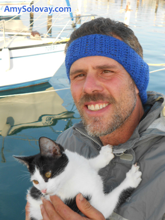 Mike Wearing a Crocheted Headband and Holding Cindy the SuperModel Kitten. A free crochet pattern is available online for the headband pattern.
