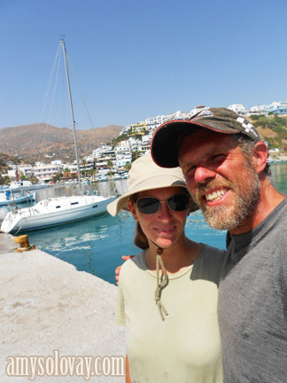 Mike and Amy Take a Self-Portrait Photo With the Beneteau Sailboat in the Marina at Agia Galini.