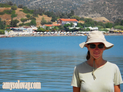 Amy in the marina at Agia Galini, Crete, with the beach in the background.