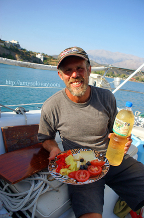Mike with a plate of Greek olives, cheese and veggies, aboard our sailboat in Agia Galini, Crete, Greece.