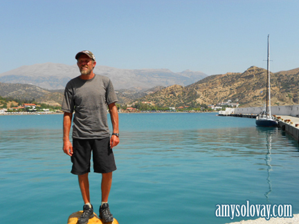 Mike with our sailboat in the background, at the Agia Galini marina, Crete, Greece.